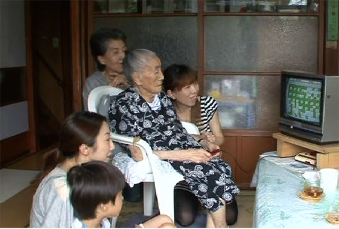 99 year old Umeji Narisawa plays her favorite videogame while her family watches