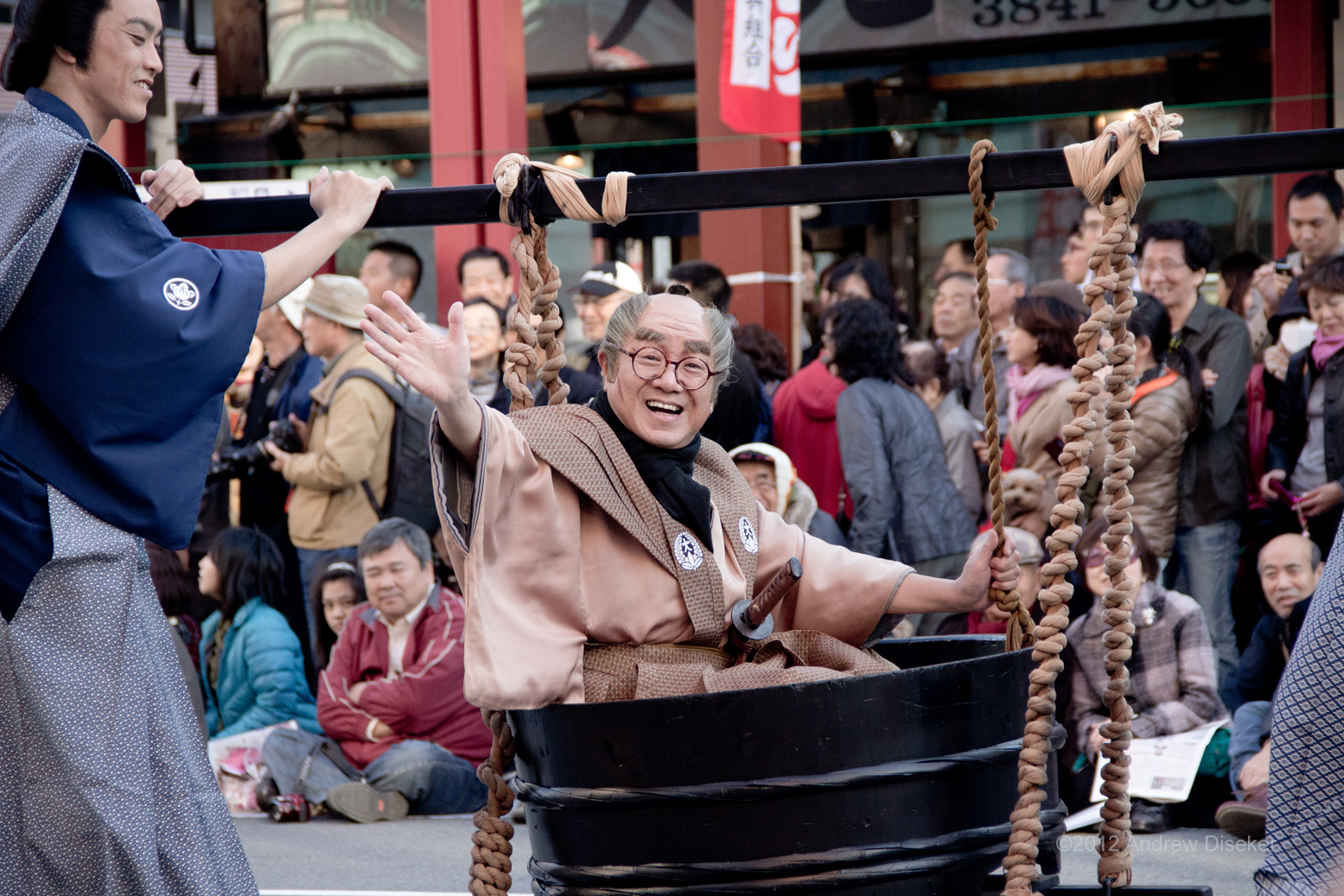 man being carried in bucket waving and smiling at the crowd